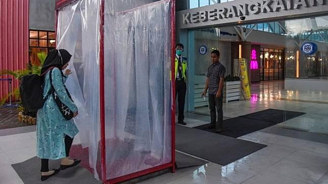 Penumpang memasuki bilik disinfektan yang terpasang di pintu keberangkatan Bandara Internasional Lombok (BIL) di Praya, Lombok Tengah, NTB, Jumat (27/3/2020). ANTARA FOTO/Ahmad Subaidi/nz