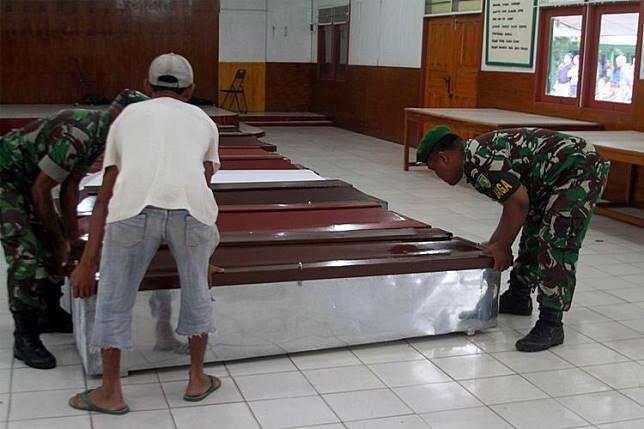 Anggota TNI dibantu warga mempersiapkan peti jenazah untuk korban penembakan Kelompok Kriminal Bersenjata (KKB) di Wamena, Papua, Selasa (4/12/2018). Sebanyak 31 karyawan PT Istika Karya diduga tewas ditembak oleh KKB saat melakukan pengerjaan jalur Trans Papua di Kali Yigi dan Kali Aurak Distrik Yigi, Kabupaten Nduga, Papua pada 2 Desember lalu. ANTARA FOTO/Iwan Adisaputra/sgd/hp.(ANTARA/IWAN ADISAPUTRA)   Artikel ini telah tayang di Kompas.com dengan judul
