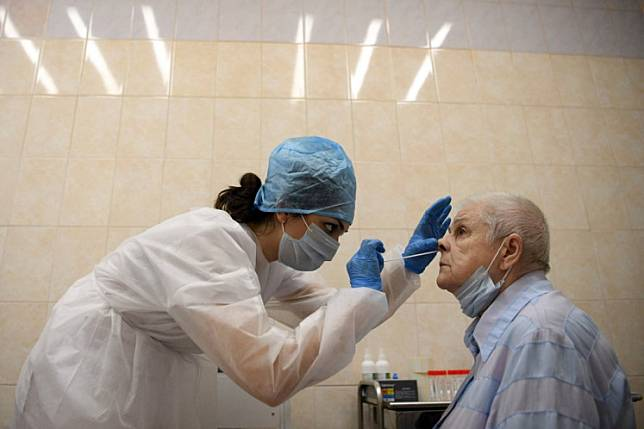 A medical worker wearing protective equipment takes a swab from a woman at a medical facility in Moscow on July 16, 2020, on the first day the Russian capital started providing free testing for the coronavirus disease to its residents.