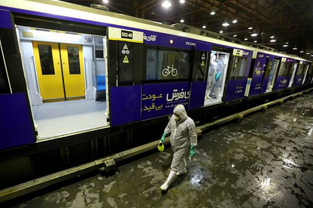 A Tehran Municipality worker cleans a metro train to avoid the spread of the COVID-19 illness on Feb. 26, 2020.Iranian authorities on Wednesday announced domestic travel restrictions for people with confirmed or suspected cases of the novel coronavirus.