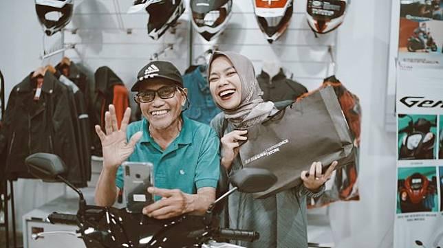 Bapak driver ojek online terlihat sumringah saat diberikan motor baru dan handphone baru