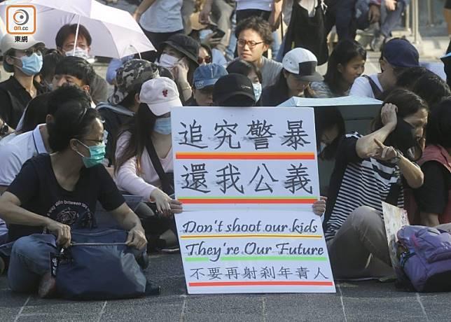 參加者在遮打花園舉起「追究警暴,還我公義」等標語。(袁志豪攝)