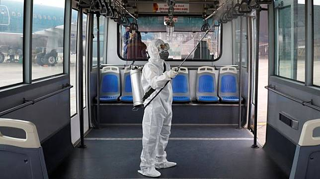 Seorang petugas kesehatan menyemprotkan disinfektan di dalam bus Vietnam Airlines untuk melindungi dari wabah Virus Corona di bandara Noi Bai di Hanoi, Vietnam, 21 Februari 2020. REUTERS/Kham