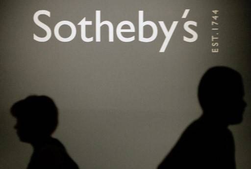 People pass by a Sotheby's auction house logo in the Russian History Museum in Moscow, 23 May 2007.