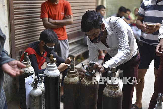Sejumlah warga menunggu untuk mengisi tabung oksigen di New Delhi, India, Kamis (29/4). Delhi melaporkan 25.986 kasus baru, 368 kematian dalam 24 jam terakhir dan terus berjuang dengan pasokan oksigen yang ada. EPA-EFE/IDREES MOHAMMED
