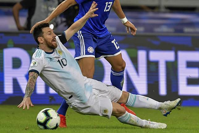 Argentina's Lionel Messi falls next to Paraguay's Junior Alonso during their Copa America football tournament group match at the Mineirao Stadium in Belo Horizonte, Brazil, on June 19, 2019.