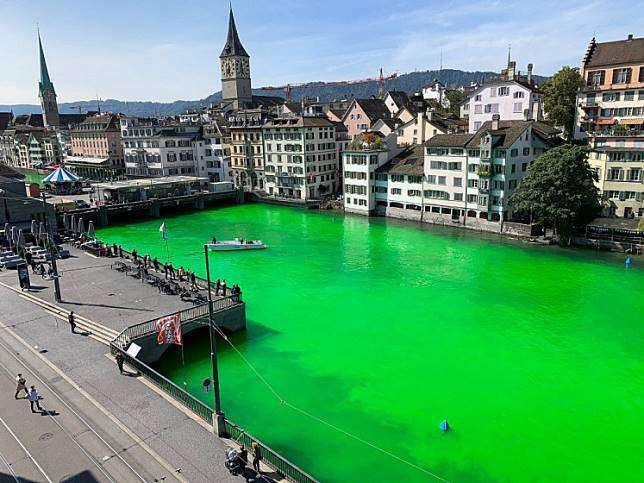 This handout picture released by the Swiss police of the city of Zurich (Stadtpolizei Zurich) shows the Limmat river dyed green during a demonstration by Extinction Rebellion Zurich at midday in the center of the city on September 10, 2019.