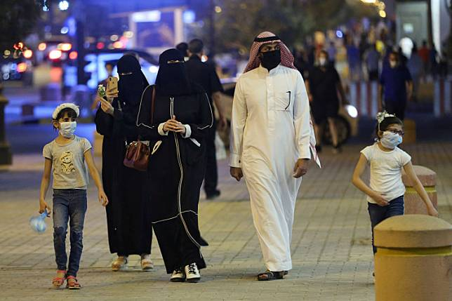 A Saudi family wearing protective face masks walk on Tahlia Street as nightlife kicks off, after the government loosened lockdown restrictions following the outbreak of the coronavirus disease (COVID-19), in Riyadh, Saudi Arabia June 21, 2020.