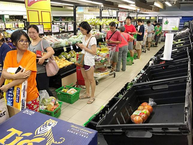 This picture provided by The Straits Times taken on March 17, 2020 shows people queueing for groceries at a supermarket in Singapore, amid concerns over the spread of the COVID-19.