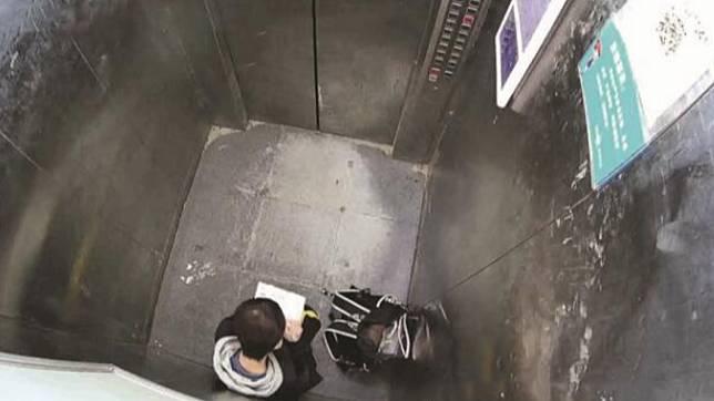 13歲男童受困電梯,淡定蹲下寫功課。(圖/翻攝自《人民網》)