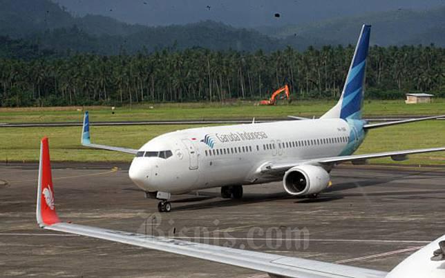Pesawat milik maskapai penerbangan Garuda Indonesia bersiap melakukan penerbangan di Bandara internasional Sam Ratulangi Manado, Sulawesi Utara akhir pekan lalu (8/1/2017)./Bisnis-Dedi Gunawan\\n