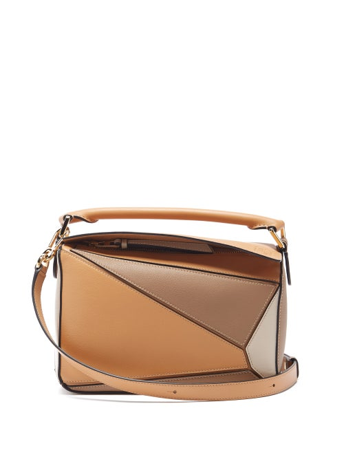 Loewe - Named by artisans for its complex 524-step assembly, Loewe's khaki-beige Puzzle cross-body bag is defined by its angular panels. It's crafted in the house's Spanish workshop from grained leather and features an Anagram-embossed flap top that opens to reveal a durable herringbone interior, then finished with lacquered edges for a graphic twist. Adjust the shoulder strap to carry it cross-body.