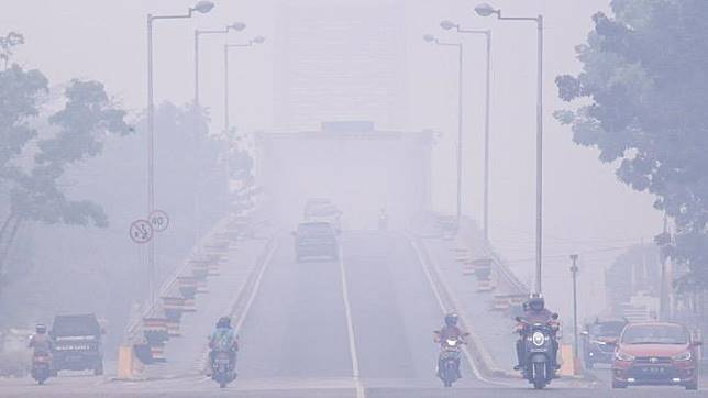 Vehicles move slowly along a smog-covered road during the haze in Palangka Raya, Central Kalimantan, Indonesia on Sunday, September 15, 2019. Schools in two cities in the Indonesian part of Borneo island will be closed for a week after smoke from forest fires caused air quality to hit
