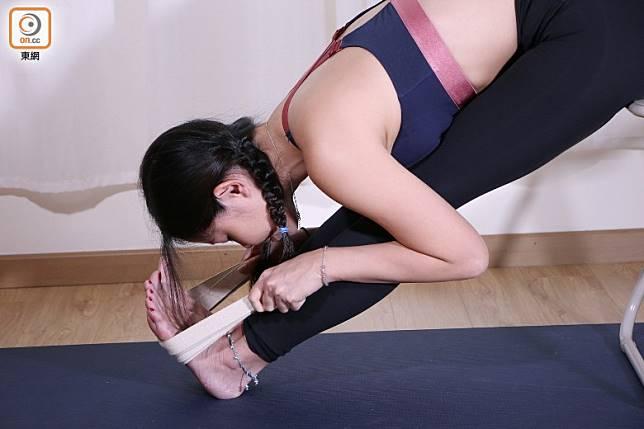 如果用雙手抓腳掌有難度,可以用毛巾或瑜伽帶輔助。(盧展程攝)