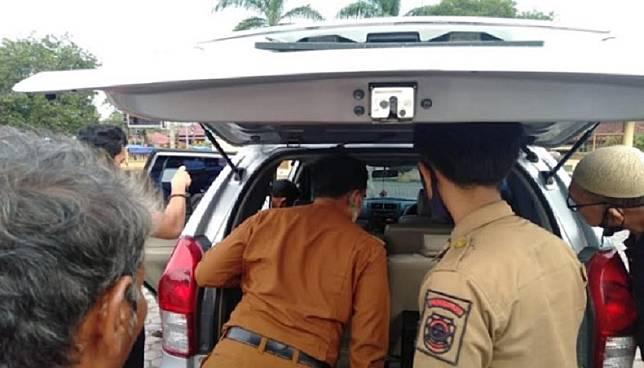Petugas kelurahan dan Satpol PP Kota Padangsidimpuan memeriksa mobil goyang yang terparkir di halaman Masjid Al Abror Padangsidimpuan. (Foto/SINDOnews/Zia Nasution).