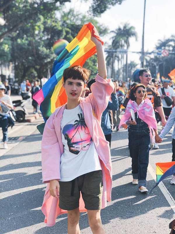 去年底剛滿20歲的鍾明軒,勇於公開性向,曾身穿粉色大衣、拿著彩虹絲巾,現身同志大遊行。(圖/翻攝自鍾明軒臉書)