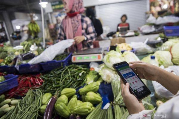 Ilustrasi : Pengemudi ojek daring menggunakan aplikasi belanja saat memesan sayur-mayur di pasar Kosambi, Bandung, Jawa Barat, Jumat (10/4)