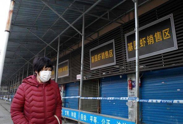 Seorang perempuan berjalan di depan pasar di Wuhan, tempat virus mirip SARS pertama kali ditemukan.