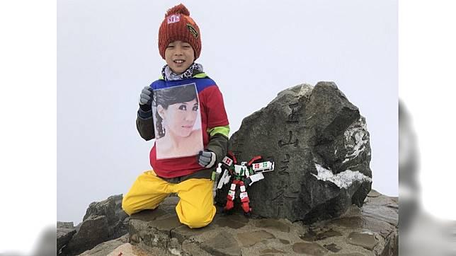 8歲的鄒澤綱帶著媽媽遺照攻頂玉山。圖/鄒品為授權使用