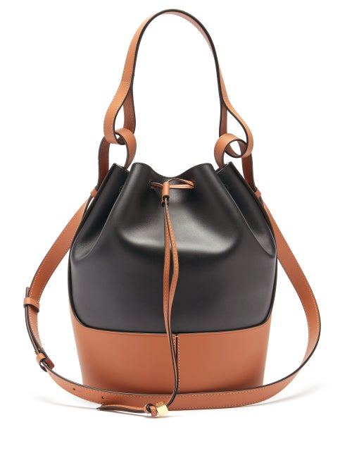 Loewe - Loewe's tan and black Balloon bag is named after the rounded silhouette which tapers to a gathered drawstring top. It's crafted in Spain from smooth leather debossed with the Anagram logo and rests on a structured base. The interlinked top handle and shoulder strap spotlight the label's affinity for experimental techniques.