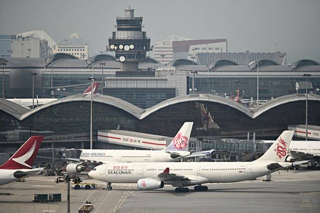A control tower (top) is seen past passenger planes at Hong Kong's international airport on March 13, 2019Airlines, airports and insurers across Asia are bracing for the prospect of unusually high damage as the region's tropical storm season begins, as hundreds of aircraft grounded by the coronavirus pandemic can't be moved easily.