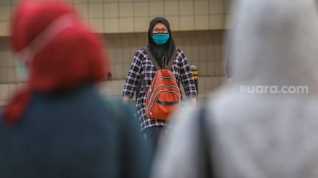 Sebagai ilustrasi: Pekerja kantoran menggunakan masker saat menyebrang jalan di Kawasan Sudirman, Jakarta Pusat, Senin (8/6). [Suara.com/Alfian Winanto]