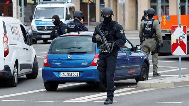 Police officers guard near the site of a shooting, in which two people were killed, in Halle, Germany October 9, 2019. Two people were killed in a shooting in the eastern German city of Halle on Wednesday, and a suspect was arrested, police said, with broadcasters showing images of an alleged perpetrator dressed in combat garb including a helmet. REUTERS/Fabrizio Bensch