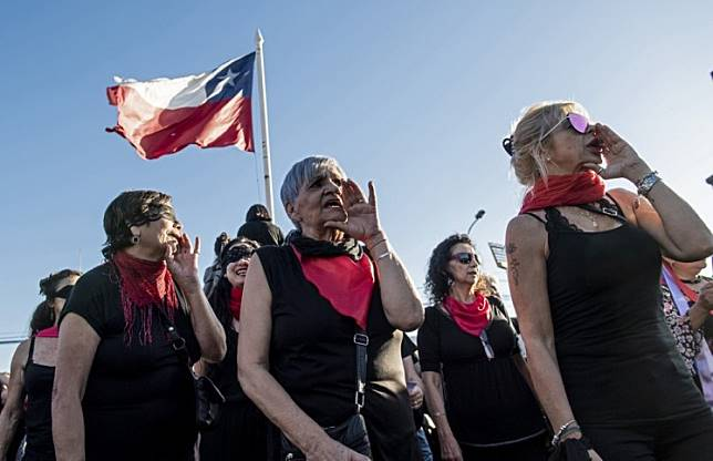 Feminist activists with a Chilean flag take part in a choreographed performance against gender violence, patriarchy and denounce an oppressive state, outside the national stadium in Santiago on December 04, 2019.