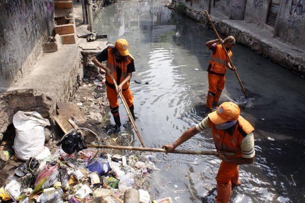 Ilustrasi: Petugas PPSU membersikan sampah di aliran Kali Krukut yang berwarna hitam pekat di Kelurahan Kebon Kacang