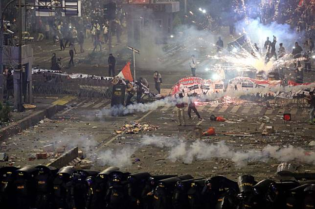 Police fire tear gas at protesters during a riot near the Elections Supervisory Agency (Bawaslu) headquarters in Jakarta on Wednesday.