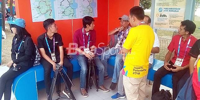 Wartawan menunggu angkutan shuttle bus dari venue tenis menuju MPC, Senin (20/8/2018) di Jakabaring Sportcity Palembang.