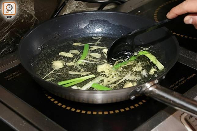用滾油爆香薑葱。(盧展程攝)