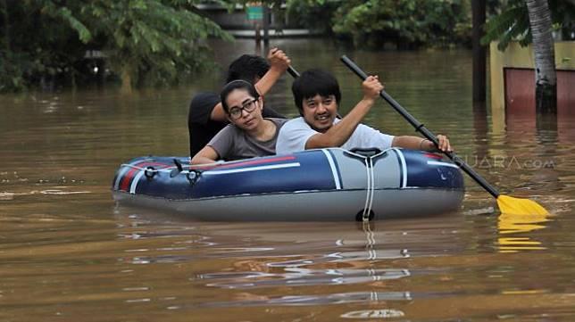 Warga melewati banjir dengan perahu di Perumahan Bumi Nasio Indah yang terendam banjir di Bekasi, Jawa barat, Selasa (25/02). [Suara.com/Alfian Winanto]