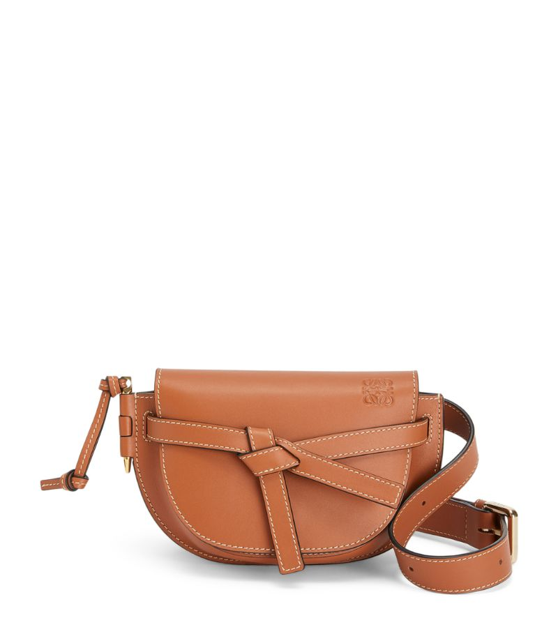 Owing its name to the latched side pin and knotted front belt closure, the coveted Gate bag from LOEWE reimagines timeless functionality with the Spanish Houses distinct contemporary aesthetic. Taking on a saddle-shaped silhouette, the cross-body design is handcrafted in smooth leather to retain its structured profile, while the iconic Anagram is embossed to the front for a sleek and instantly recognisable finish.