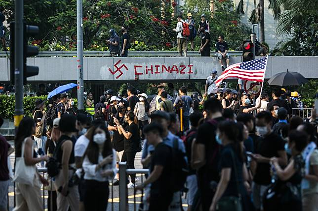 Demonstrators walk past a swastika and the word