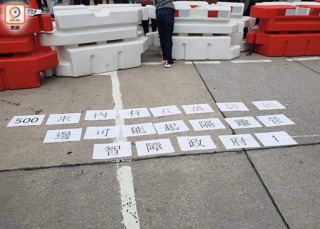 居民在地上貼標語。(梁裔楠攝)