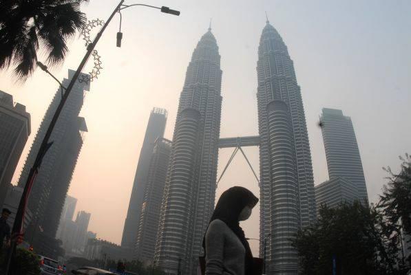 Warga beraktivitas dengan mengenakan masker di dekat menara kembar Petronas, Kuala Lumpur, Malaysia
