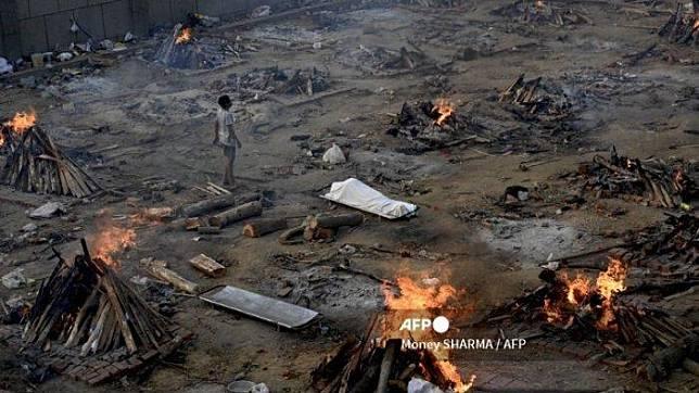 Seorang pria berdiri di tengah pembakaran para korban yang kehilangan nyawa karena virus Corona Covid-19 di tempat kremasi di New Delhi India pada 26 April 2021.