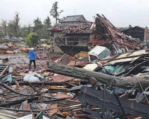 Topan Hagibis yang berkekuatan dahsyat melanda Jepang disertai dengan hujan deras, kemarin. (Foto kiri) rumah-rumah hancur setelah diterjang