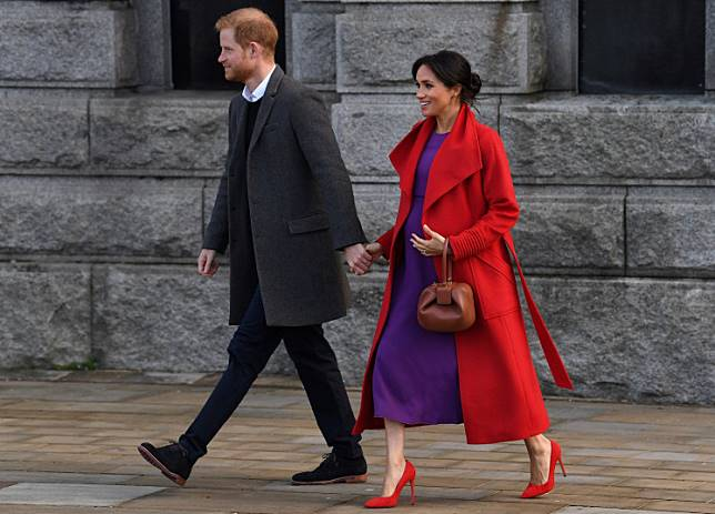 Britain's Prince Harry, Duke of Sussex (L) and his wife Meghan, Duchess of Sussex react during their visit to Birkenhead, northwest England on January 14, 2019.