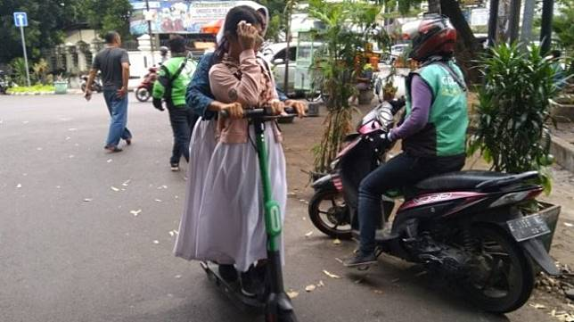 Siswi salah satu sekolah menggunakan skuter elektrik tanpa helm di kawasan Wijaya, Jakarta Selatan, Jumat (15/11/2019). [Antara/Laily Rahmawaty]