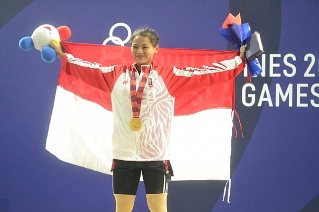 Indonesian weightlifter Windy Cantika Aisah holds the national flag after winning gold in the women's 49 kilogram category at the 30th Southeast Asian Games in Manila, the Philippines.