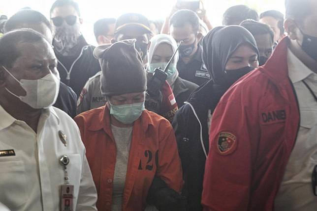 Loan fraud suspect Maria Pauline Lumowa (center, in orange shirt) arrives at Soekarno-Hatta International Airport on Thursday under the escort of National Police personnel and the Law and Human Rights Ministry's extradition team.