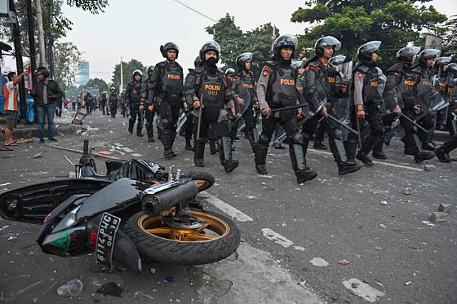 Indonesian anti-riot police take a position to disperse the mob during an overnight-violent demonstration near by the Elections Oversight Body (Bawaslu) in Jakarta on May 22, 2019. - Indonesian police fired tear gas to disperse demonstrators in downtown Jakarta early Wednesday after a rally opposed to President Joko Widodo's re-election, an AFP reporter said.